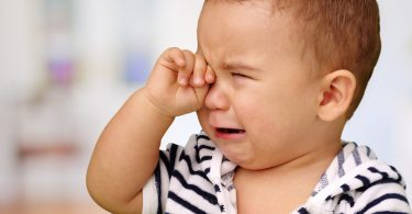 A baby is crying because he is sick.