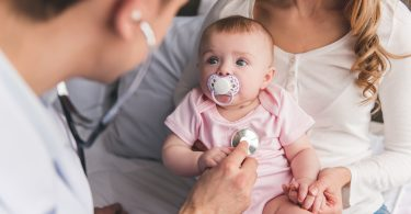 Baby looks at doctor while he's listening to her lungs.