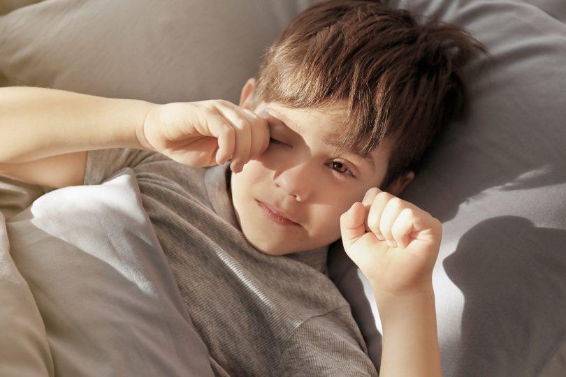 Little boy rubbing irritated eyes