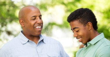 African American father talking to his teen son.