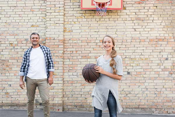 Daughter playing basketball with her dad