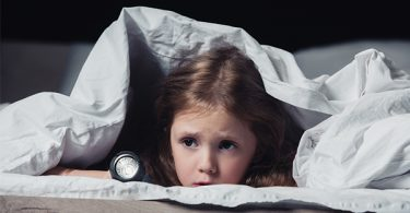 Little girl hiding under blanket with a flashlight because she is scared of the dark