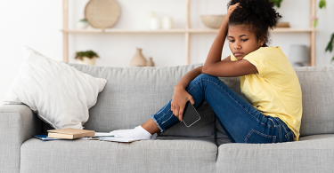 Black female teenager on sofa depressed