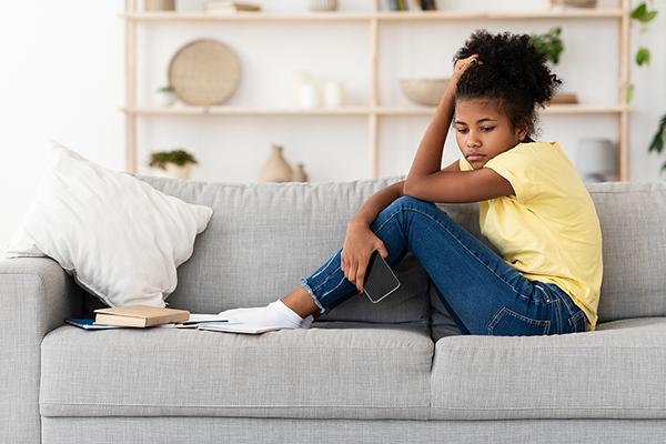 Black female teenager on sofa depressed