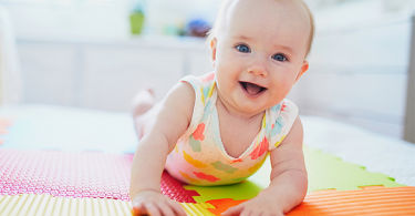 Baby smiling on colorful mat