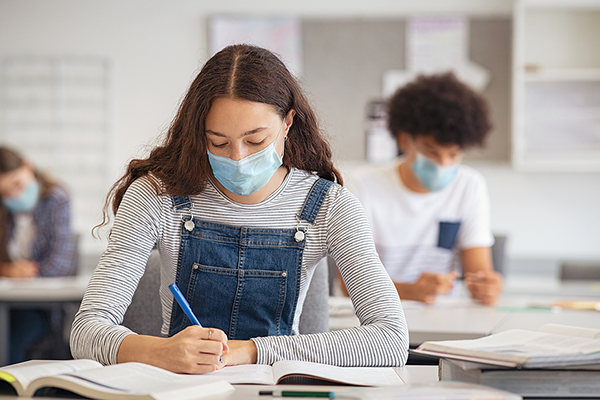 Students wearing a mask in high school classroom.