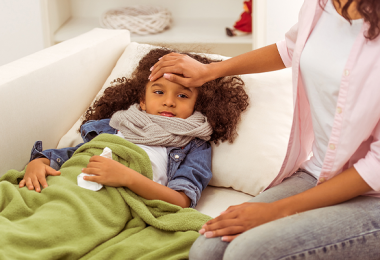 Young girl sick on sofa and mother taking temperature