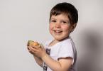 Little boy eating avocado