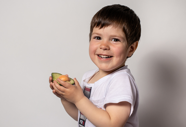 Little boy eating avocado