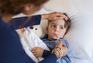 Mom taking son's temperature with thermometer