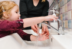 Little girl washing her hands