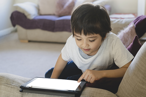 Little boy playing on tablet.