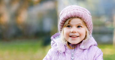 Little girl outside in cold weather wearing a hat and jacket