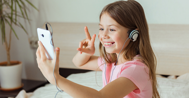 Child smiling talking to friend on video call